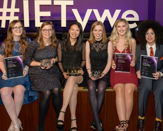 Photograph of six women in eveningwear (some dresses, one suit) holding their metallic awards or framed finalist certificates