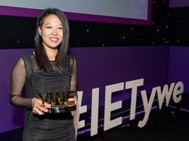 Ying Wan Loh wearing a black evening dress, holding her gold award. She is in front of the a display with the words #IETywe. Ying is a young Asian woman with shoulder length hair and an undercut. Her dress is black with see-through sleeves.